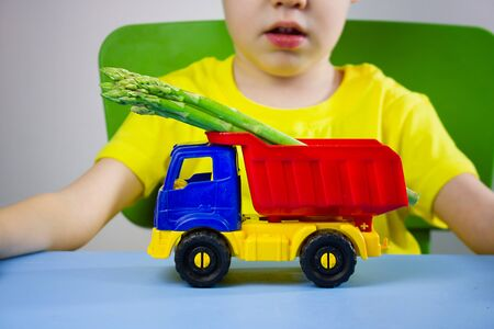 Toy car truck with asparagus in the back on a table in front of a child. Playing with food, feeding children is healthy food in a playful way Banque d'images