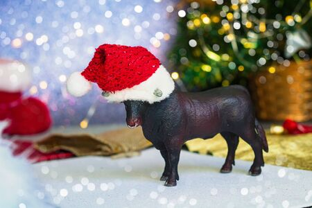 bull as a symbol of the new year and christmas 2021 on shiny christmas tree background and decor