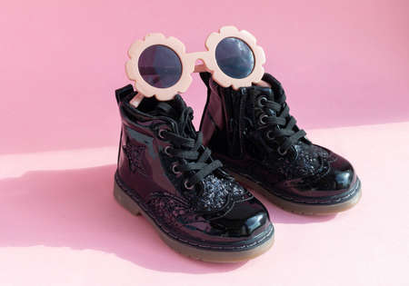 Patent childrens boots shoes and accessories for little fashionistas on a pink background