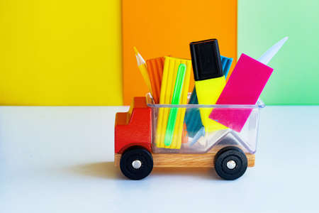 A set of school supplies and stationery for primary school children and kindergartens copy space. Delivery and fun workplace concept. Organizer toy car