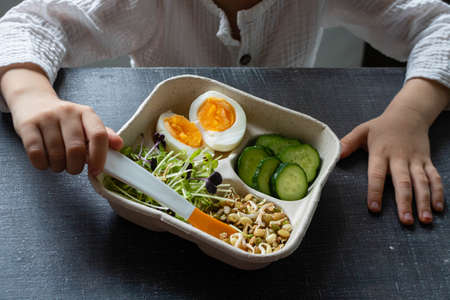 Close-up top view food - eggs, salad, a mixture of sprouted grains and seeds and vegetables. Childrens hands on a gray dark background. Eating healthy food for children
