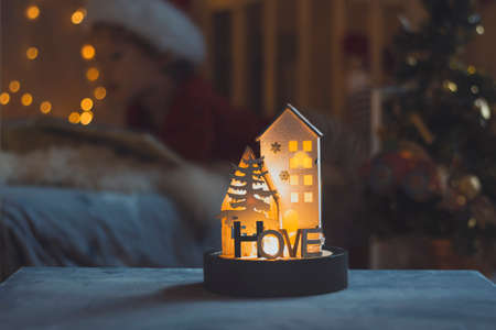 lamp in form of a house with text home on background of a cozy apartment interior with a blurred bokeh garland. Blurred child reads a book. The dark trendy style is toned. Home and family concept