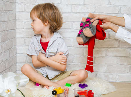 The child plays on the floor with feet. Womens hands stretch out warm clothes - socks and a scarf. The boy doesnt want to get dressed. Maternal care and anxiety concept