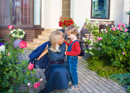 A child and an older woman hug and happily chat in the flower yard in front of the cottage. Grandmother greets her grandson. Joint time of the elder and the younger. Generational love Archivio Fotografico