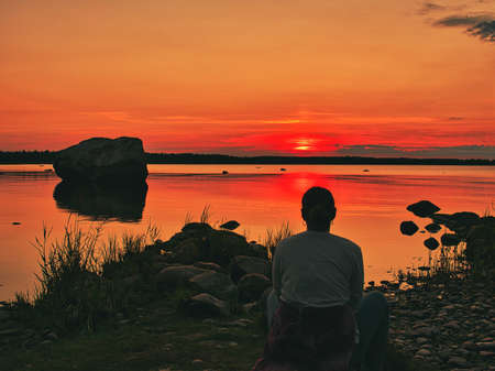 A woman sitting on the shore of the Baltic Sea with a beautiful sundown.