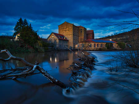 A mill at a river with high water in the evening