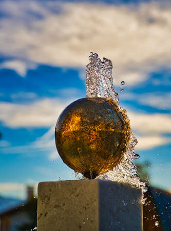 A little fountain in a brass / golden ball with water coming out.