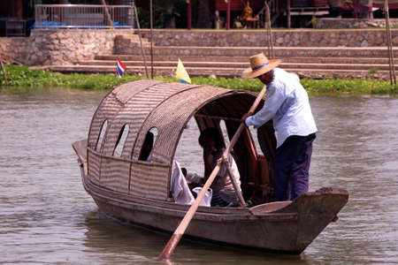 padding: Asian wood paddling ferry boat across the river