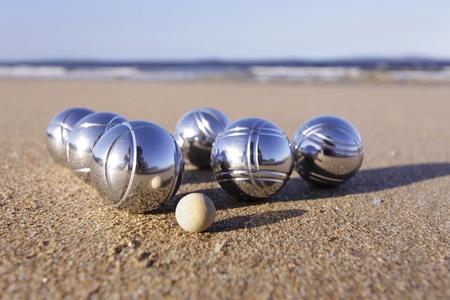 120404-14 Un conjunto de seis Boule petanca y un cochonnet en una playa de arena