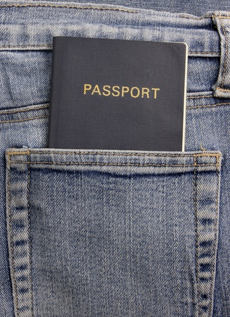 A generic blue passport in the back pocket of a  pair of faded blue denim jeans. Stock Photo