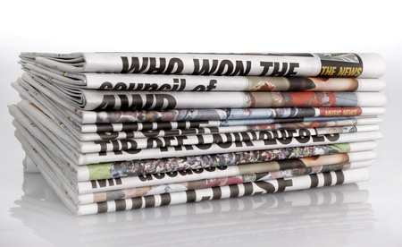 Stack of newspapers on white background. photo
