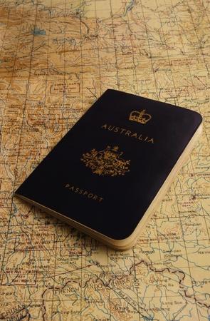 An old Australian passport sitting on an old map. Stock Photo