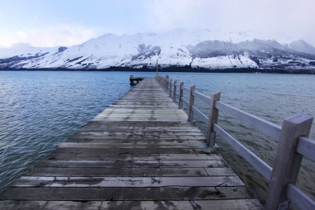 A wharf  on Lake Wakatipu in winter with snow covered mountains. Glenorchy, South Island, New Zealand.   photo
