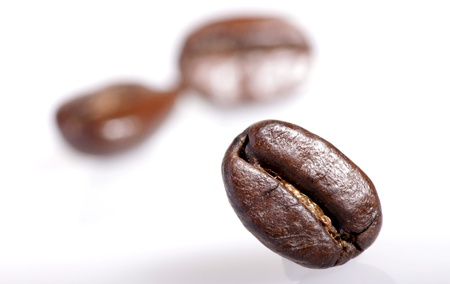 sharply: One roasted coffee bean sharply in focus with two out of focus beans in background on white. Stock Photo