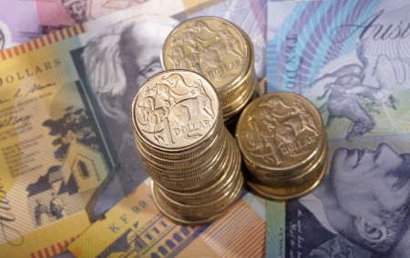 Three stacks of Australian one dollar coins on a background of bank notes  photo