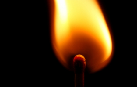 ignited: Flame from a single lit match isolated on black background.