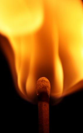 matches: A r�fagas partido en llamas en que se enciende en un fondo negro. Foto de archivo