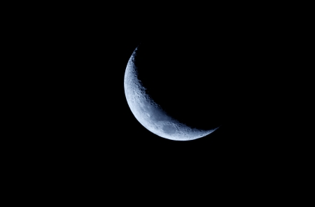 A Blue Crescent Moon against a black sky. Stock Photo