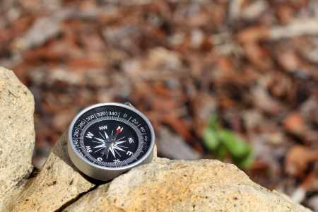 An antique compass with the needle pointing North resting on a rock. Stock Photo - 17155898