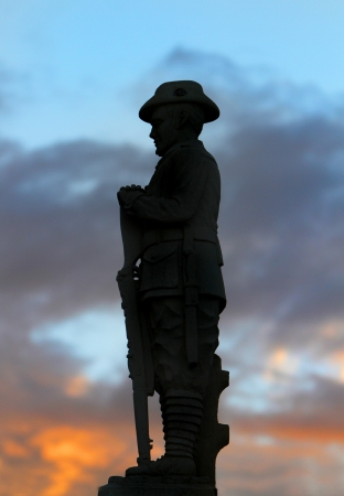 anzac: ANZAC Memorial of Australian digger with a rifle silhouetted against a sunset sky with orange and blue.