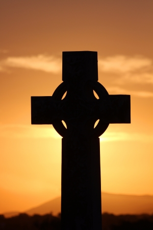 memorial cross: Cruz celta en silueta contra una puesta de sol de color naranja.