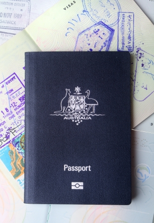 Australian passport sitting on open passports showing pages and visa stamps