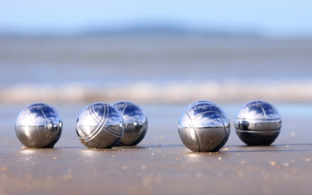 bocce: A set of steel bocce balls on a sandy beach. Stock Photo