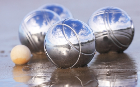bocce: Four chrome boules and a cochonnet on a wet sandy beach.