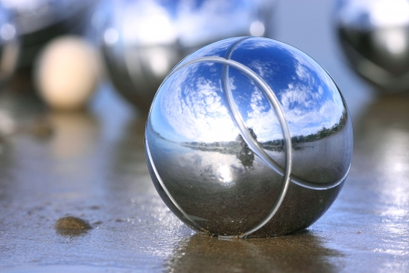 boules: A steel petanque ball on a sandy beach with other boules in the background.