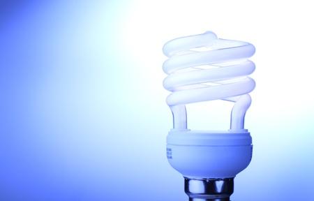 id�e lumineuse: Illumin� glob lumi�re fluorescente compacte sur fond bleu, avec copie espace symbolisant une id�e lumineuse. Banque d'images