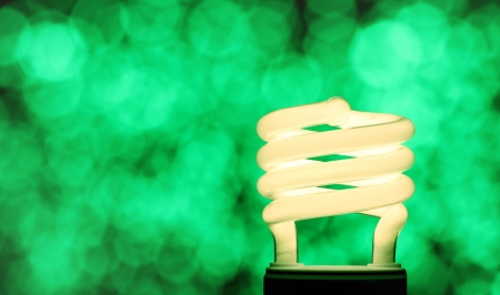 Illuminated compact fluorescent lamp  - CFL - on a background of de-focused green lights symbolising energy efficiency - with copy space. photo