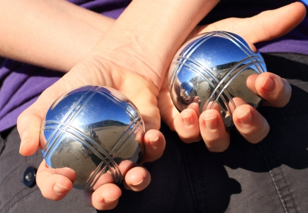 bocce: A woman holding two chrome boules behind her back.