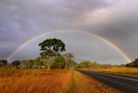 Early morning rainbow over an outback country road in Australia photo