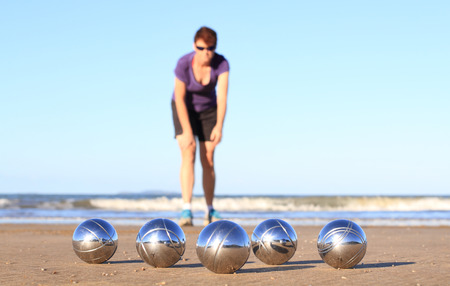 A woman playing boules on a beach.