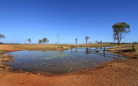 waterhole: Pozo de agua interior de Australia, Billabong con cerca r�stica, suelo rojo y el azul cielo