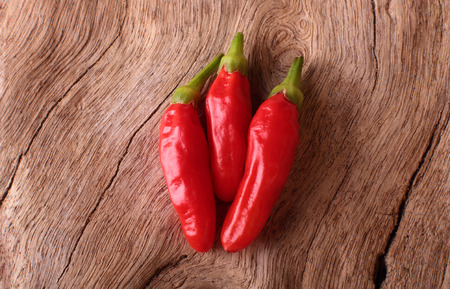 piri piri: Three Red piri piri chilli peppers on a rustic timber background.