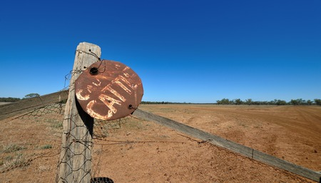 A Caution Cattle Sign made from the top of a oil drum wired to a fence in Western Queensland between Tambo and Charleville.   Photo CHRIS ISON