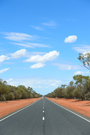 red soil: Australian outback two lane highway with red soil, green bushland and blue cloud sky.  Photo Chris Ison.