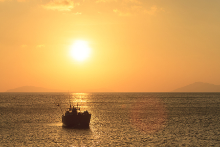 Orange sun sets over the ocean with a fishing boat in the foreground in tropical Northern Queensland, Australia with copy space