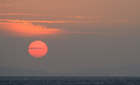Sunset over the ocean with clouds in front of a big red disc sun. Stock Photo