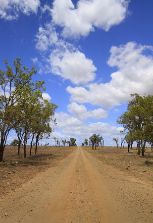 An unsealed rural road with blue sky and clouds in outback Queensland Australia