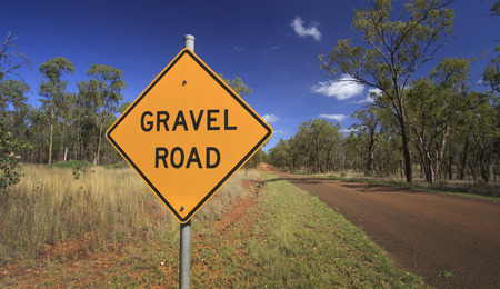 Outback Australian road with warning sign of gravel ahead with blue sky and red soil.