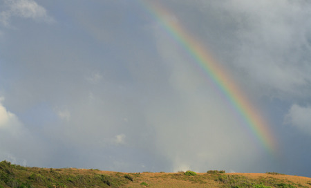 A partial rainbow touching the the land with clouds and copy space.