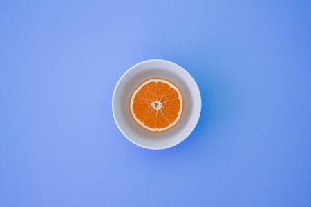 Minimal photo of fresh orange on plate on bright background. Фото со стока