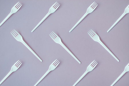 Flay lay photo of white plastic disposable forks. Creative top view pattern. Фото со стока