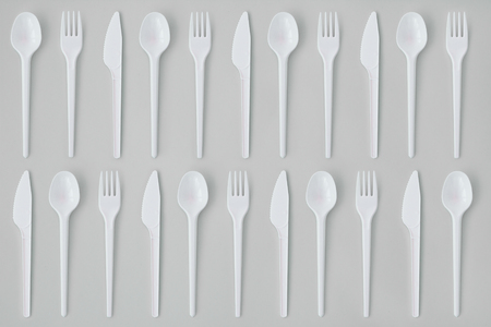 Flay lay photo of white plastic disposable forks, spoons and knives. Creative top view pattern. Фото со стока