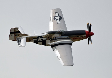 Fly by of a P-51D Mustang. Powered by a Merlin V-12 Rolls Royce engine, one of the best aircraft ever made.