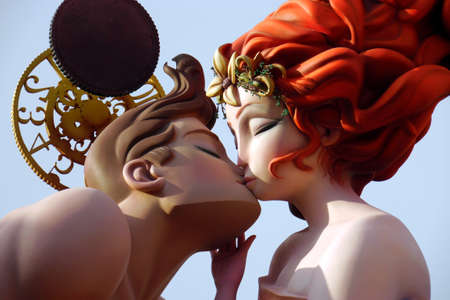 Colorful papier mache figures giant Fallas festival of kissing in Valencia, sculpture of ninots under blue sky. Couple kiss. Girl with red hair boy with brown hair kissing.
