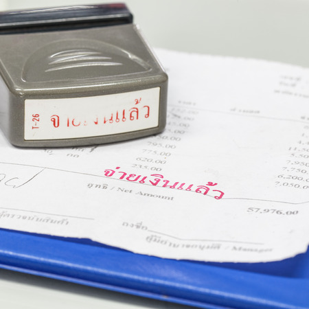 paid stamp: Close-up picture of an invoice on blue clipboard with red paid stamp. Stock Photo