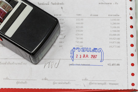Close-up picture of an invoice on red clipboard with date stamp. photo